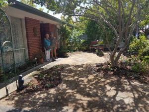 Lawn removed, garden beds, path and seating area.