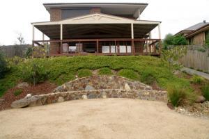 Coldstream Rock retaining wall doubles as seat, Sloping garden bed, Diamond creek back garden.